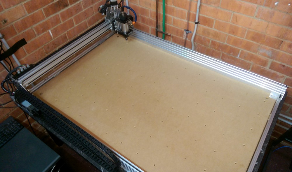 Photo of CNC bed with holes for inserts